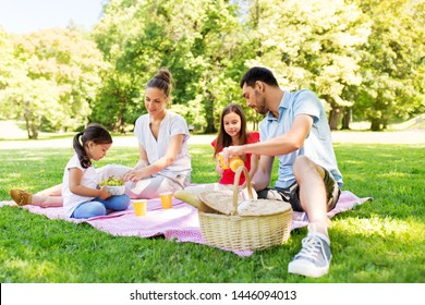 family, leisure and people concept - happy mother, father and two daughters having picnic at summer park