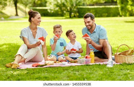 family, leisure and people concept - happy mother, father and two little sons having picnic and eating watermelon at summer park