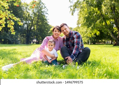 family, leisure and people concept - happy mother, father and little son at summer park