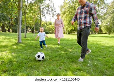 family, leisure and people concept - happy mother, father and little son with ball playing soccer at summer park