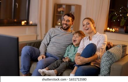 家族と余暇、人々のコンセプト – 幸せな笑顔の父、母子、リモコンと息子が、家で夜にテレビで何か面白いものを見る