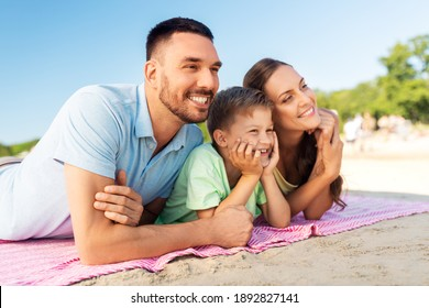 family, leisure and people concept - happy mother, father and son lying on summer beach