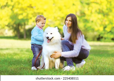 Family, leisure and people concept - mother and child walking with dog in warm sunny day