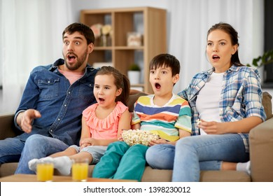 family, leisure and people concept - scared or surprised mother, father, son and daughter with popcorn watching horror on tv at home