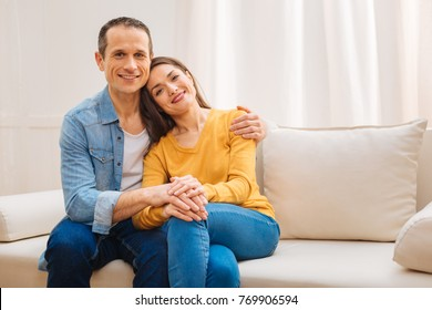 Family life. Gay cheerful loving couple smiling to the camera  while hugging and sitting on the couch