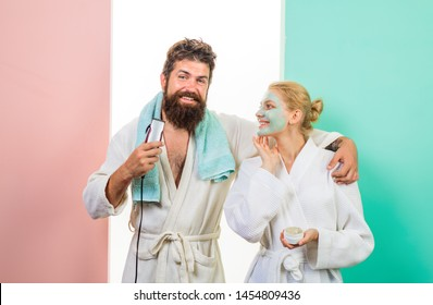 Family life. Husband and wife. Bearded man with electric shaver trimming beard. Happy woman with cosmetic facial mask. Morning treatments. Morning routine. Morning procedures. Couple. Relationship.