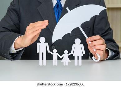 Geschäftsmann schützt Familienmitglieder, z.B. Eltern und zwei Kinder.