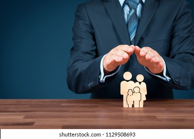 Family life insurance, services and supporting families concepts. Businessman with protective gesture and wooden figurines representing young insured family.