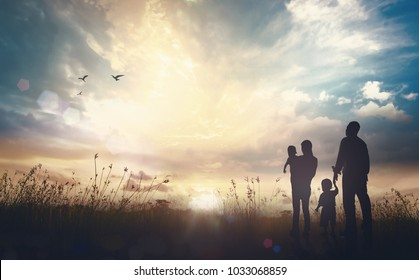 The family life journey concept: Father, mother and two son over meadow sunset background