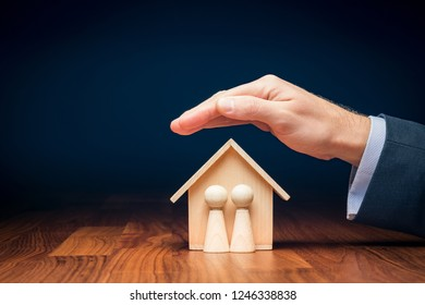 Family life and property insurance concept. Wooden figurines representing family and wooden house and businessman hand with protective gesture, symbol of insurance.
