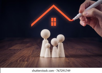Family life and property insurance concept. Wooden figurines representing family and hand drawing house, symbol of insurance.