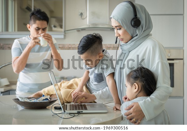 Family lifestyle concept, Multitasking mother, work with her laptop and taking care of the family