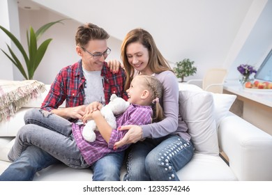 family lifestyle portrait of a mum and dad with their children having good time at home