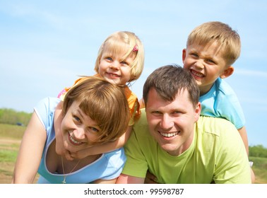 family lifestyle portrait of a mum and dad with their children having good time on the green grass