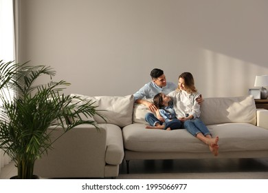 Family with little daughter resting on sofa in living room - Shutterstock ID 1995066977