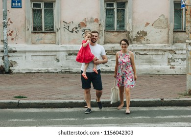 Family with little girl walking in city street