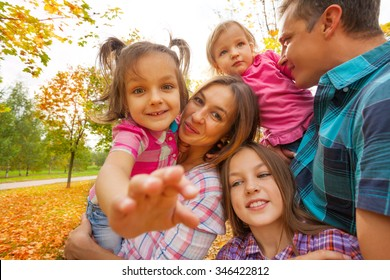 Family with little kids sit, play in autumn park