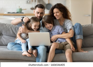 Family with little kids spend time together seated on couch in living room with laptop planning holidays tour booking hotels, e-commerce, apps users, shoppers choose on-line services and goods concept