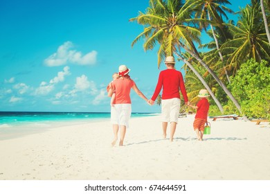 family with little son and daughter walk on beach