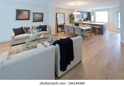 Family, living room with dining table and the luxury modern kitchen at the back. Interior design.