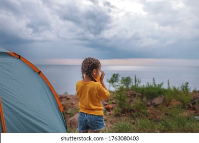 Family local getaway. Kid sitting in the camping tent at campsite and looking at sunset, healthy active lifestyle, safe summer staycation after lockdown
