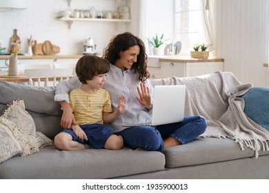 Family, lockdown. Happy mother and kid son greeting online, waving hands, looking at web camera laptop for video call sitting on couch at home. Smiling mom and child having fun talking in video chat .