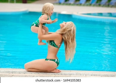 Family look, swimwear outfit. Beautiful blond mother with her pretty daughter having fun and relaxed by swimming pool on villa beach. Summer time vacations.