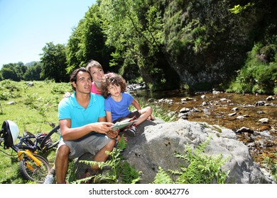 Family looking at map by mountain river