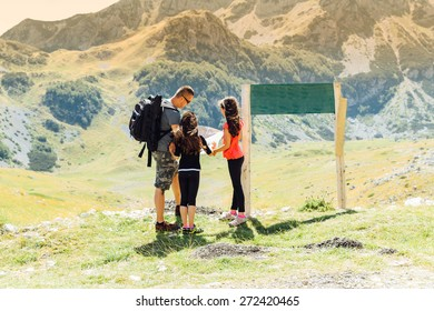 Family looking at map on near national park sign a hiking day.Happy family in mountains discussing the route.Family on mountain trek.
