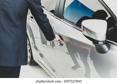 Family looking for new car with salemans hand on handle opening a car door in matte
