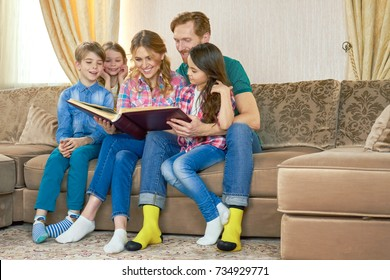 Family looking at photo album. Happy people sitting on sofa. Family tree research.