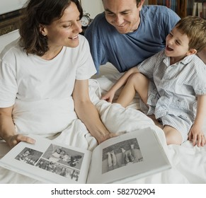 Family Looking Photobook Together at the Bedroom
