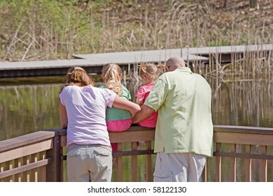 Family Looking at the Water on the Dock