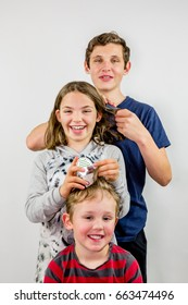 Family louse treatment. Three children comb each others hair to look for head lice, smiling and laughing.