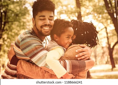 Family love. African American family hugging in park. Close up.