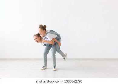 Family and love concept - happy twin girl giving piggyback ride to her laughing sister