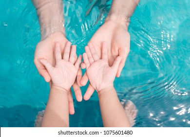 Family Love. Daughter hand in her Mother hand at pool.