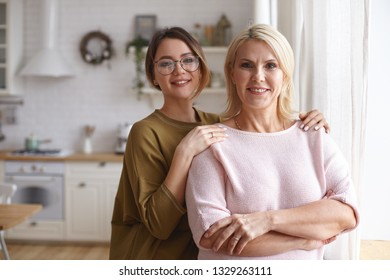 Family, love and happiness concept. Happy cute young female in stylish eyeglasses posing n blurred kitchen embracing her attractive joyful middle aged mother, having fun together, smiling happily