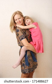Family love happy blond mother and daughter having fun hug in dress. studio