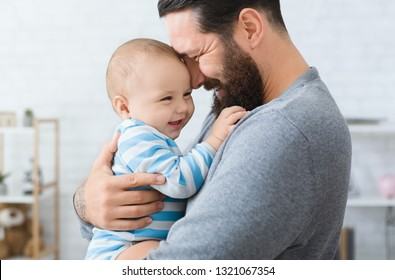 Family love and joy. Happy father embracing with his laughing adorable baby