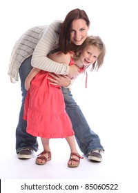 Family love of mother and daughter having fun hug with happy laughter. Girl is six years old wearing coral red dress while mother wearing blue jeans and long cardigan.