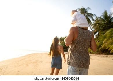 family in love on the beach with son are playing at sunset