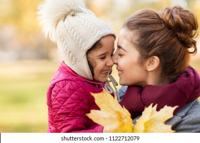 family, love and people concept - happy mother and little daughter with autumn maple leaves rubbing noses