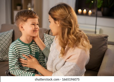 family, love and people concept - happy smiling mother talking to her little son in evening
