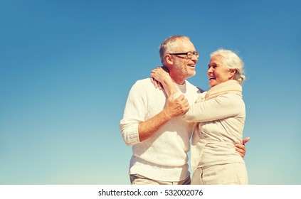 family, love and people concept - happy senior couple hugging outdoors