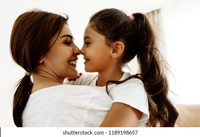 Family. Love. Togetherness. Mom and daughter are hugging, touching with their noses and smiling; at home