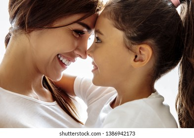 Family. Love. Togetherness. Mom and daughter are hugging, touching with their foreheads and smiling; at home
