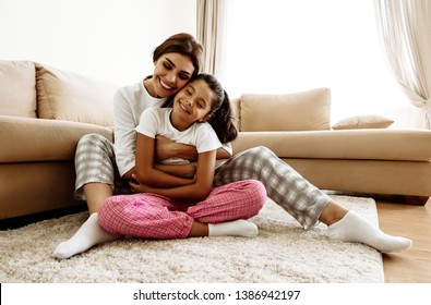 Family. Love. Togetherness. Mom and daughter in pajamas are hugging and smiling while sitting on the floor at home