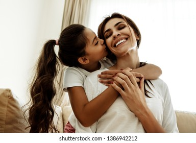 Family. Love. Togetherness. Mom and daughter at home. Girl is kissing her mom in cheek, woman is smiling