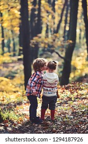 Family love and trust. Little boy kiss small girl friend in autumn forest. Brother kiss sister with love in woods. Valentines day concept. Childhood friendship and children early development.